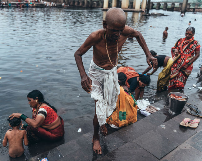 Holy bath. Every year, thousands of people from across Maharashtra come together to celebrate this 800-year old tradition called Wari. Along the way, every village, town and every city adds to this celebration of tradition. I've tried to capture a part of this journey from the eyes of a street photographer. This gentleman is getting ready after taking a bath in the local river and is about to start for his journey. Streetphotography Culture Pune Wari Varí Culture And Tradition Traditional Festival The Traveler - 2019 EyeEm Awards Musician Men Performance Musical Instrument City Arts Culture And Entertainment Togetherness Plucking An Instrument Shirtless The Street Photographer - 2019 EyeEm Awards