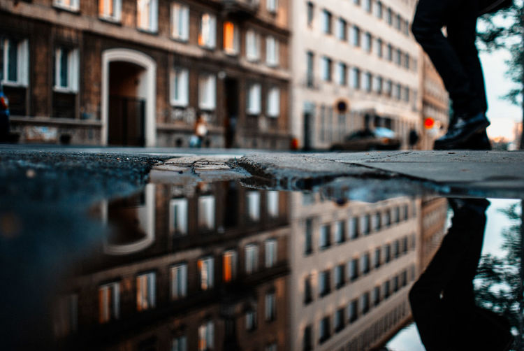 Reflection Of Building On Puddle In City