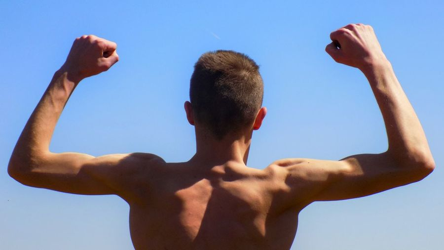 Rear View Of Shirtless Man Flexing Muscles Against Clear Sky