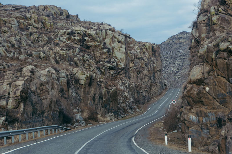 Beauty In Nature Curve Day Landscape Mountain Mountain Road Nature No People Outdoors Physical Geography Road Rock - Object Rock Formation Scenics Sky The Way Forward Tranquility Transportation White Line Winding Road