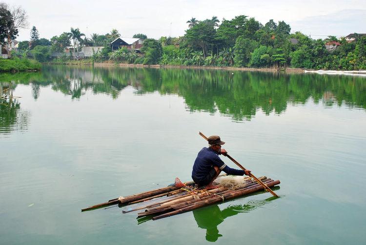 Man sailing on wooden raft in lake