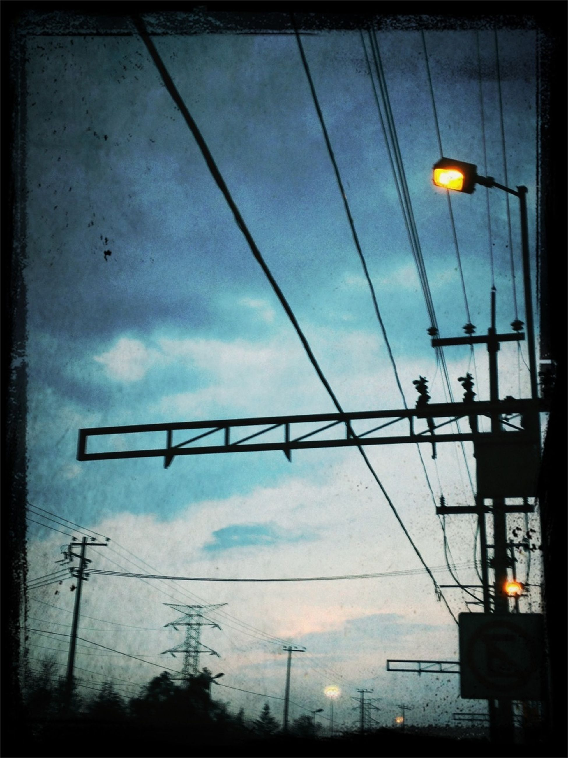 low angle view, sky, power line, electricity, lighting equipment, street light, cloud - sky, cable, silhouette, power supply, illuminated, connection, transfer print, electricity pylon, built structure, auto post production filter, dusk, cloud, cloudy, hanging