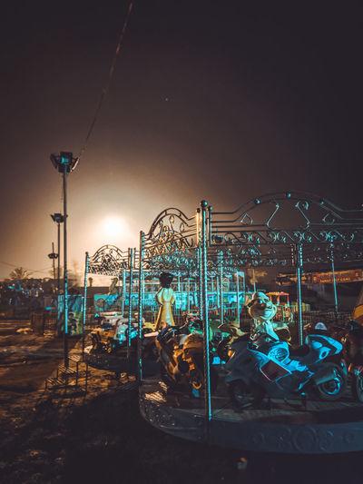 Amusement park ride against sky at night