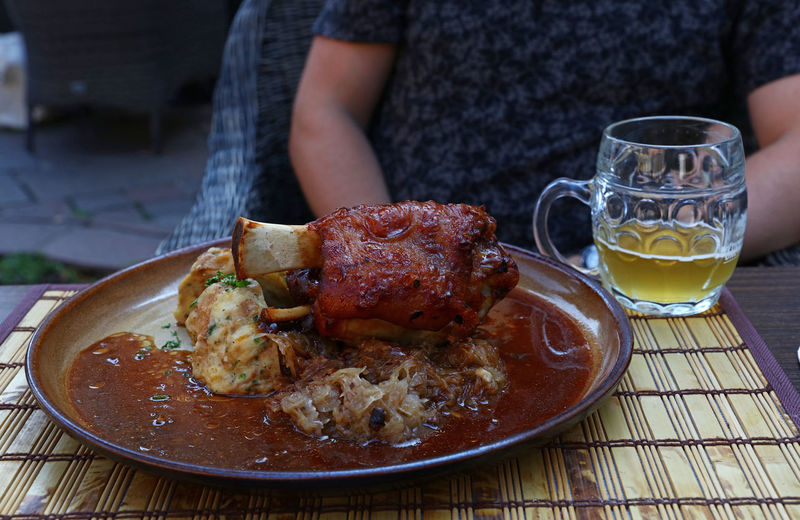 Midsection of man sitting with food and beer on table