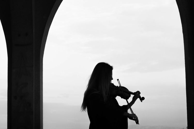 Silhouette woman playing violin against sky