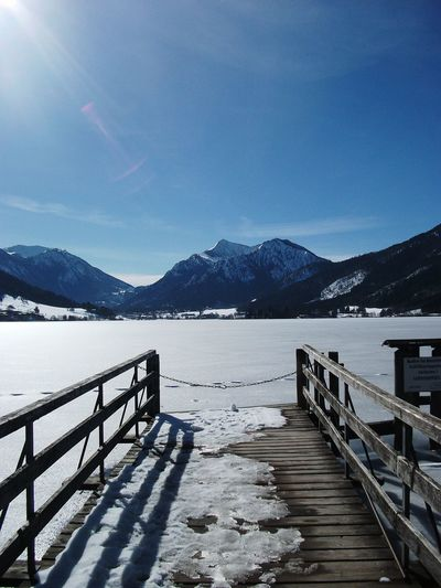 Scenic view of lake by snowcapped mountains against blue sky