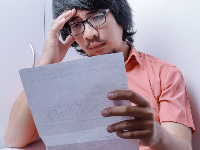 Stressful looking Asian man in Coral Pink shirt staring at his bill in his white office background Eyeglasses  Front View Glasses One Person Young Adult Holding Indoors  Real People Lifestyles Casual Clothing Paper Portrait Leisure Activity Activity Looking Young Men Young Women Contemplation Studying Stress Man Stress