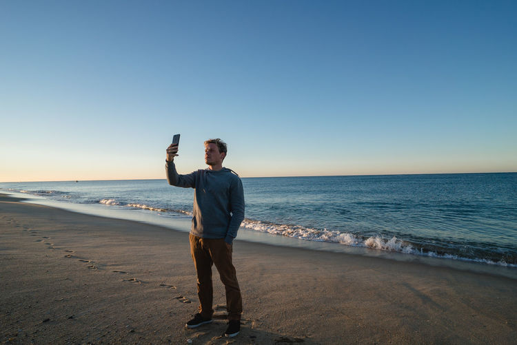 Full Length Of Man Taking Selfie At Beach Against Clear Sky