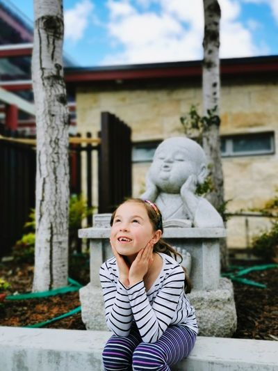 Cute girl looking up while standing against sculpture