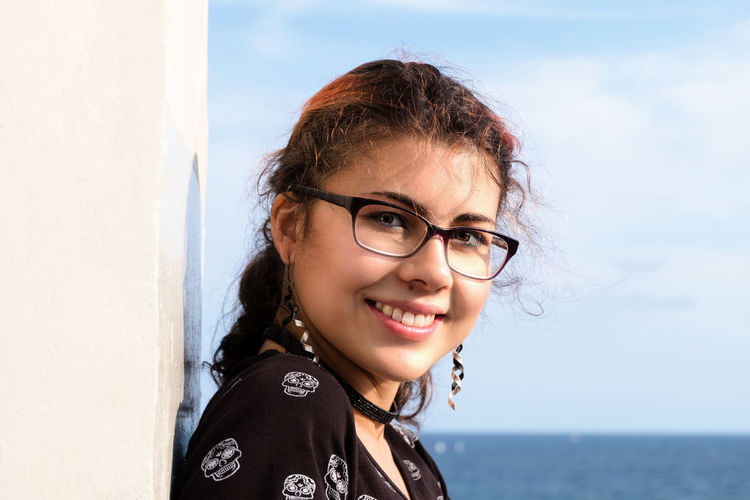 Portrait of an attractive and young woman smiling. She is wearing glasses and is leaning against a wall with the ocean in the background. The woman is part Caucasian, part Nepalese, giving her an international look. EyeEmNewHere Adult Beautiful Woman Casual Clothing Day Emotion Eyeglasses  Glasses Hairstyle Happiness Headshot Leisure Activity Lifestyles Looking At Camera One Person Outdoors Portrait Sea Sky Smiling Water Waterfront Women Young Adult Young Women