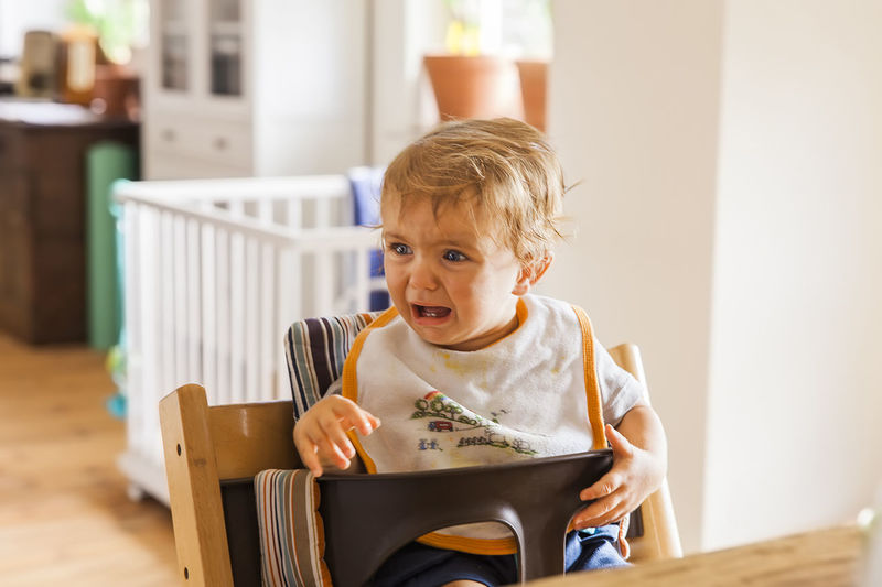 Cute baby girl crying while sitting on high chair at home
