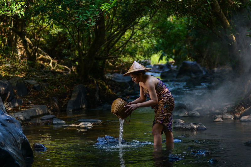 Side view of woman with basket standing in river at forest