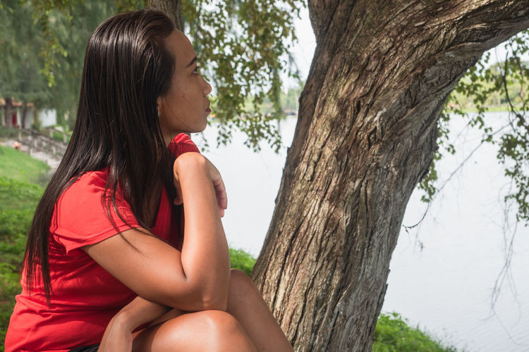Side view of young woman sitting on tree trunk