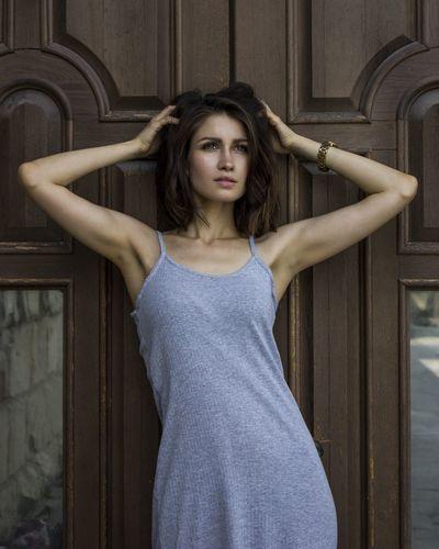 Young woman standing against door