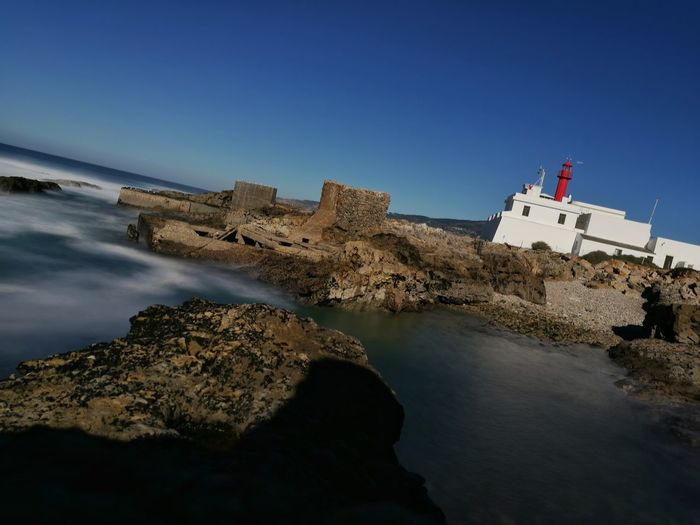 Portugal Outdoors Guincho, Portugal Lighthouse Lighthouse_captures Rocks Sea Destinations Destinationearth Longexposure Sky Earth Vacations Bridge - Man Made Structure Nautical Vessel Business Finance And Industry Architecture Water No People Day