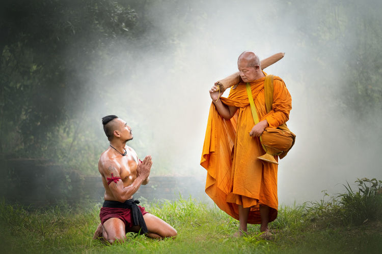 Thai ancient warriors pay respect to Buddhist old monk in the forest. Asian  Buddha Foggy Weather Man Sunlight Thailand Tree Acient Adult Culture Day Forest Full Length Gay Grass Mensfashion Monk  Outdoors Pay People Shirtless Standing Two People Wacth Worrier