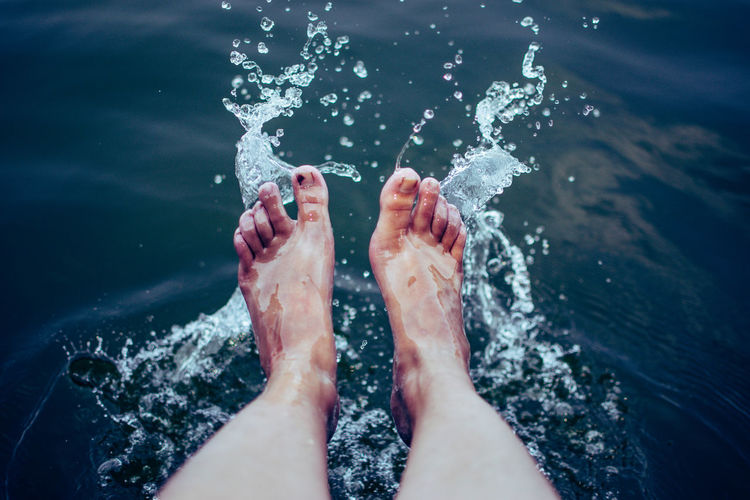Low section of person feet in sea