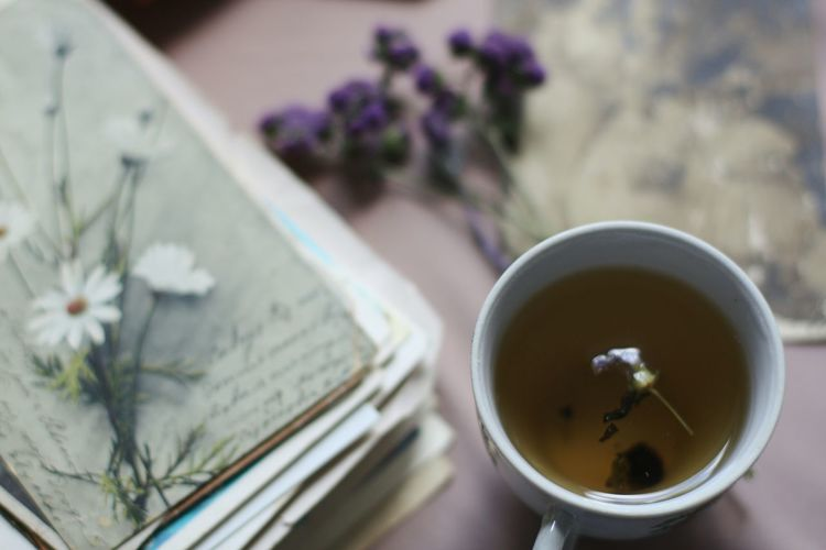 High Angle View Of Herbal Tea By Stacked Books On Table