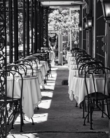 Empty dining tables and chairs on the porch of a restaurant in Lambertville, New Jersey. Absence Architectural Column Armchair Arrangement Chair Day Electric Lamp Empty Furniture In A Row New Jersey No People Place Setting Repetition Restaurant Seat Tourism Travel