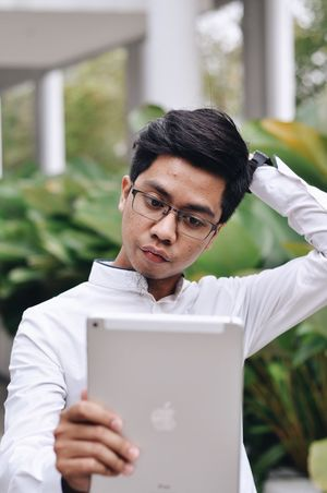 Mobile Conversations Portrait One Person Black Hair Front View Eyeglasses  Looking At Camera Technology Headshot Lifestyles Real People Day Young Adult Outdoors EyeEmNewHere Only Men One Man Only Close-up Nature Adult