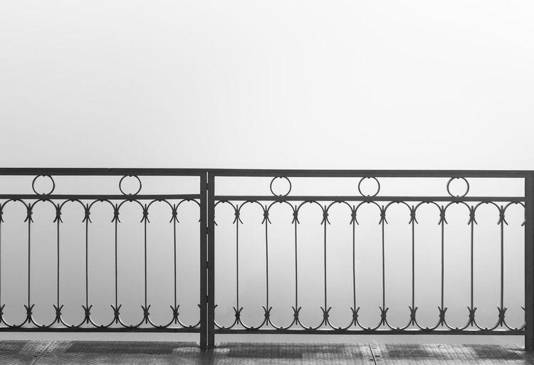 Metal railing by sea against clear sky