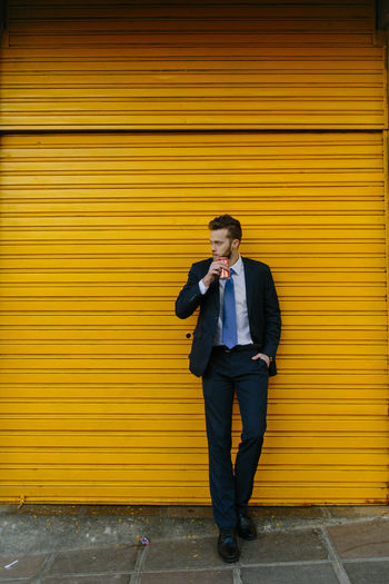 Full length of a young man standing against yellow wall