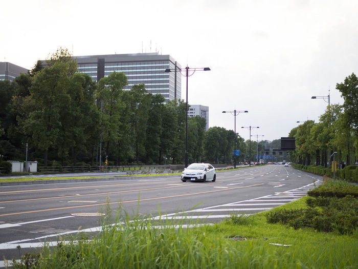 Cars on road with buildings in background
