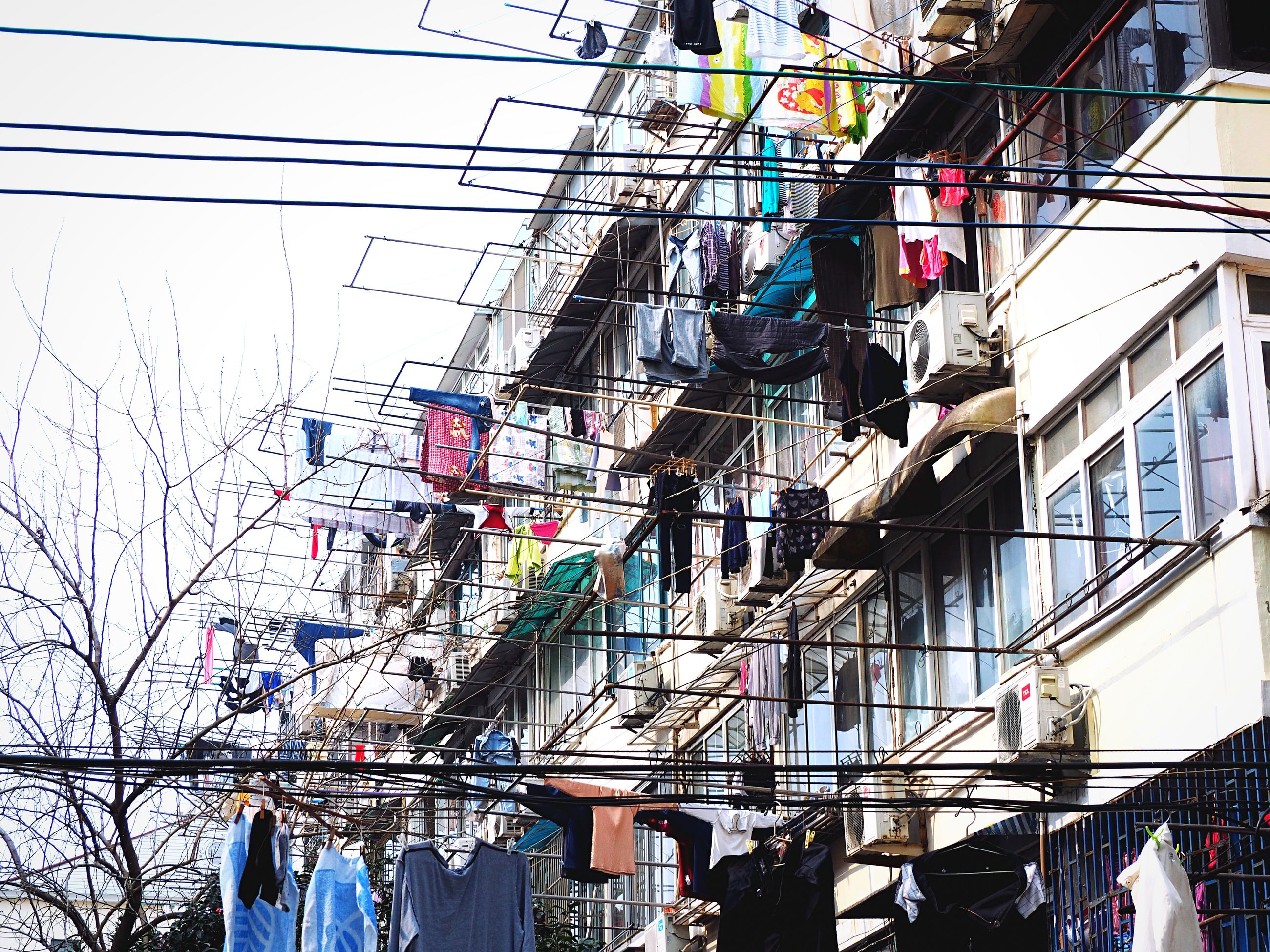 building exterior, built structure, architecture, cable, low angle view, power line, hanging, day, power supply, electricity, building, residential structure, electricity pylon, city, outdoors, residential building, no people, clothesline, wire, window