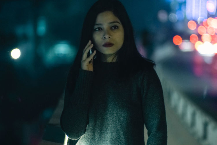 Close-Up Of Young Woman Talking On Mobile Phone At Night
