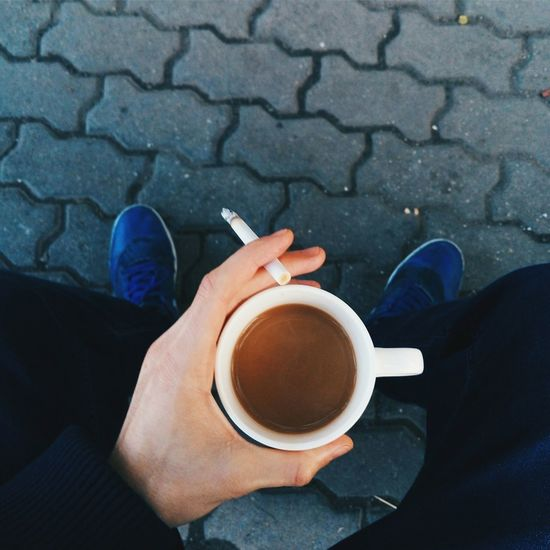 Low section of man holding cigarette and coffee cup