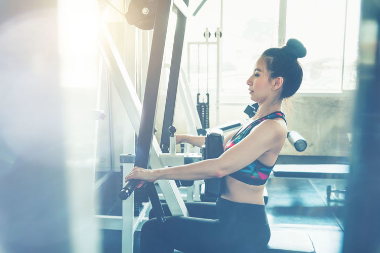 Side view of young woman exercising in gym