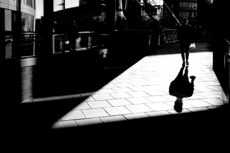 Silhouette man walking on sidewalk in city