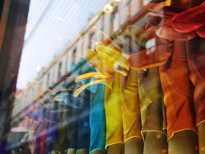 Low angle view of multi colored gloves hanging on street