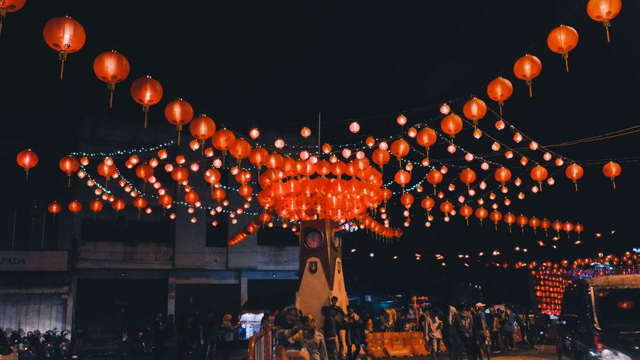 Illuminated lanterns hanging against sky at night