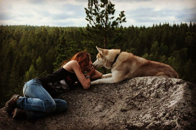 Side view of young woman with siberian husky lying on rock formation