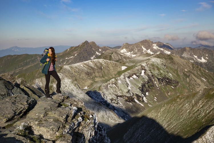 Woman standing on mountains against sky