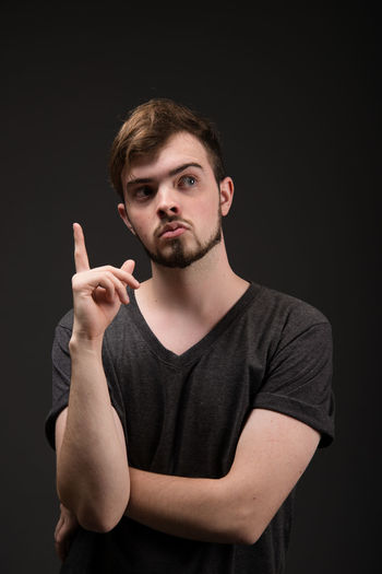 Thoughtful Young Man Gesturing While Standing Against Black Background