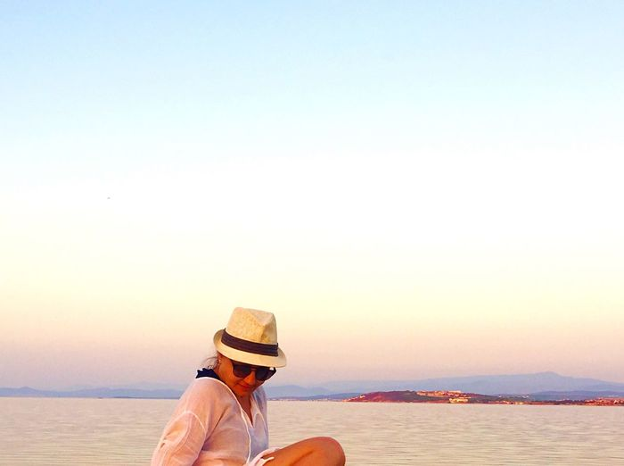 Hat Copy Space One Person Water Sea Clear Sky Beach Leisure Activity Outdoors Real People Lifestyles Vacations Nature Sun Hat Rear View Scenics Sunset Tranquil Scene Women Beauty In Nature