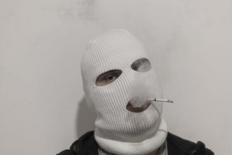 Portrait of person in mask smoking cigarette against wall