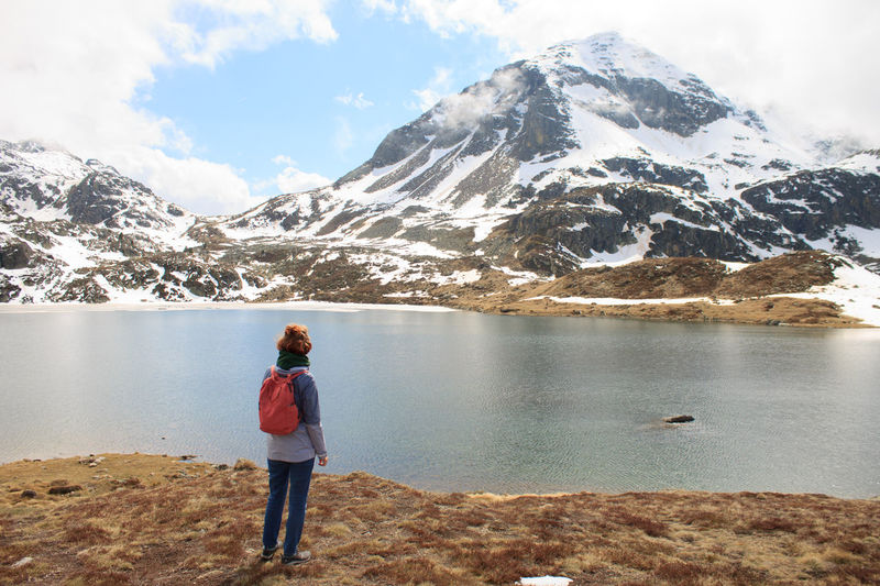 Rear view of woman standing by lake against mountain