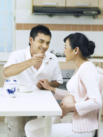 husband feeding pregnant wife 9 Months Expecting Feeding  Growth Love Married Maternity Relationship Day Time Development Fertile Fertility Kitchen Newlife Nutrient Nutriment Pregnancy Pregnant Responsibility Sitting Smiling Spouse Taking Care Togetherness Two People