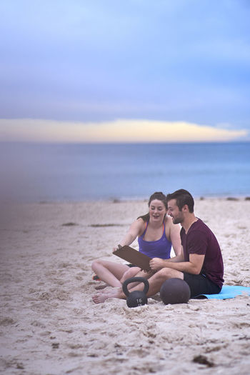 Young Friends Discussing While Sitting On Exercise Mat At Beach