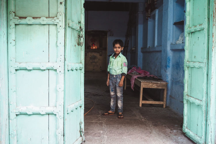 Full length portrait of boy standing against door of building