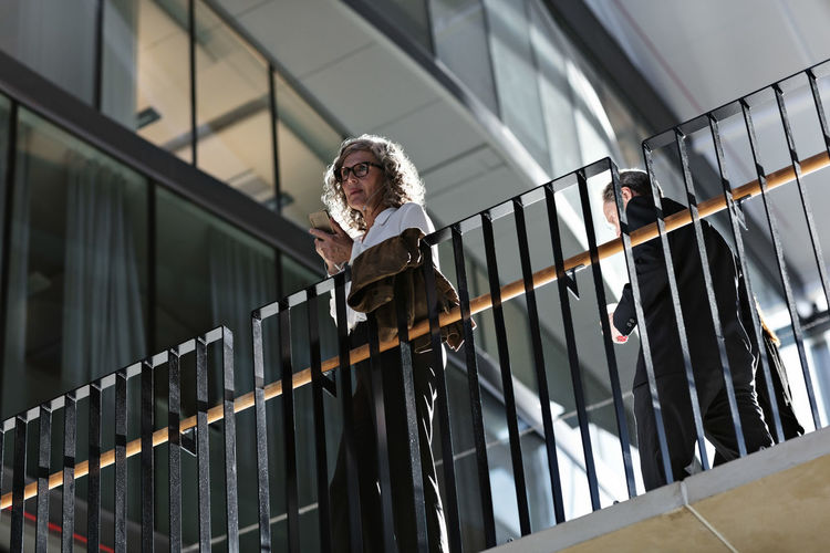 Low angle view of man standing by railing against building