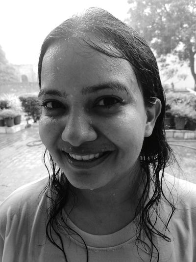 Close-up portrait of smiling wet young woman outdoors