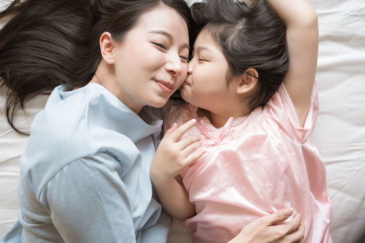 Daughter kisses her mother's cheek. and hugging in the bedroom .Happy Asian family Asian  Family Happiness Happy Happy People Family Time Home House Daughter Parent Father Mother Dad Mom Love Lifestyles Living Room ASIA Japanese  Korean Thai Taiwan Bedroom Bed Kiss Smiling Smile Fun Portrait Girls Hug Hugging Embracing moments of happiness Morning Wake Wakeup Wake Up