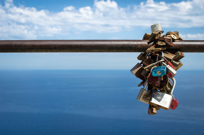 Close-Up Of Padlocks On Railing Against Sea