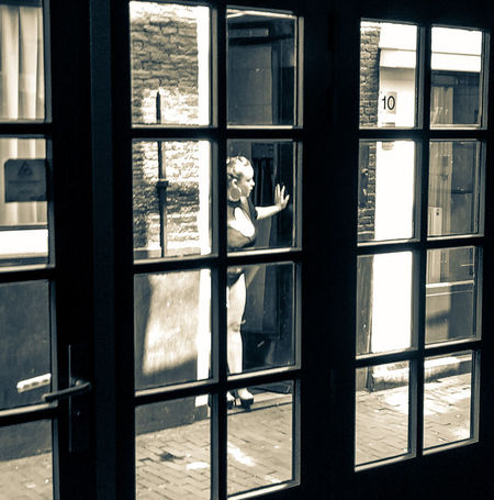 Red light district in Amsterdam. Window Day Looking Through Window Streetphotography Cellphone Camera Cellphonephotography EyeEmNewHere The Week On EyeEm Cellphoneshot Cellphone Photography Popular On Eyeem Amsterdam Redlightdistrict Netherlands Waiting For You Real Life Real People Daily Life Blackandwhite Black And White Photography Black And White Windows And Doors Windows