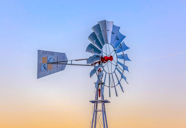 Windmill against clear sky during sunset