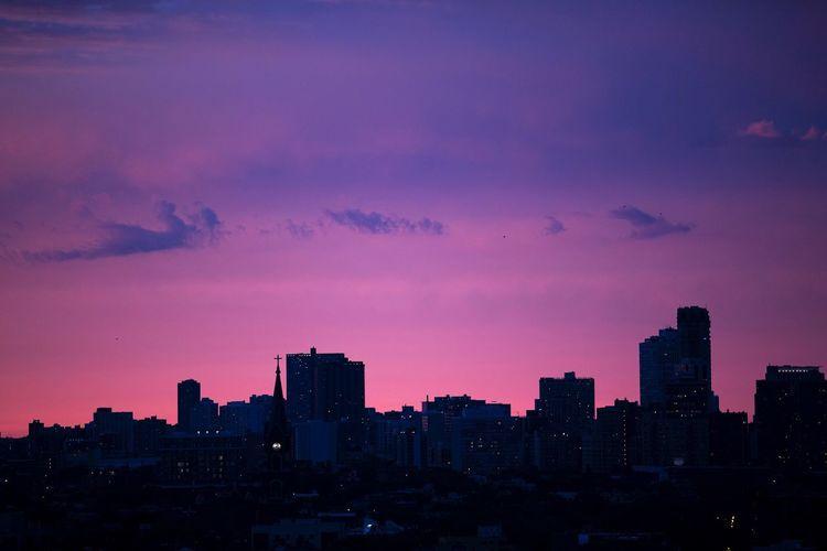 Illuminated cityscape against sky at sunset